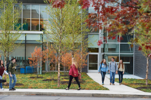 students walk out of learning commons fall foliage